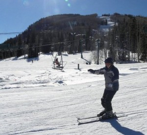 Zakya, a Below Knee Amputee, is pictured skiing down a large hill in the wintertime wearing her prosthetic.