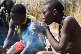 Young Tanzanian boy feathers the fire