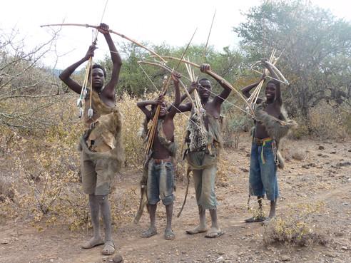 Tanzanian tribal men demonstrate their archery skills