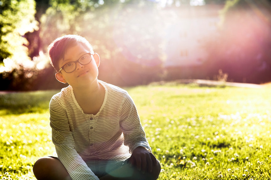 Boy with down syndrome sitting in the grass with the sun shining on his face