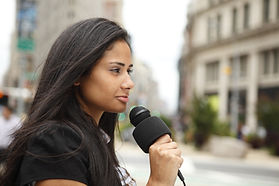 A female newscaster talking into her mic