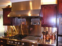 Stainless Steel Countertop, Stainless Steel Backsplash, Copper Fixtures, Range Hood, Custom Cabinets