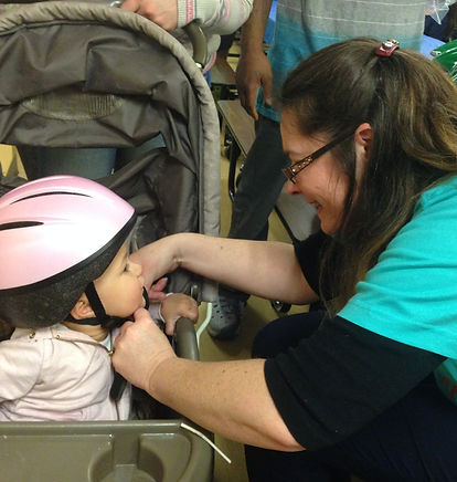 Volunteers fit children with bicycle helmets donated by the CIBA Foundation