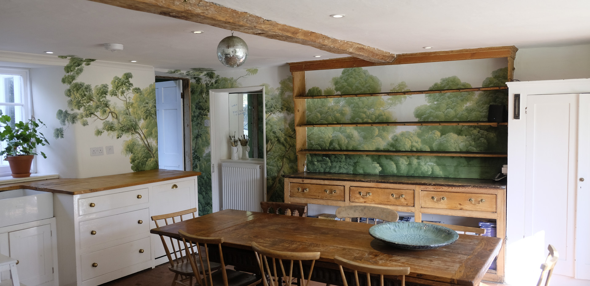 An Eighteenth century Welsh Dresser and crisp white custom fittings in the kitchen create a classic English but rather hip ambience which the various shades of my green foliage are designed to set off.