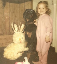 Naomi as a young girl in footsy pajamas holding the collar of a black and tan dog sitting next to her.