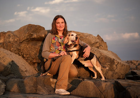 Naomi sitting on large rocks at the beach with an Beagle standing with 2 front feet on her lap looking out into the distance.