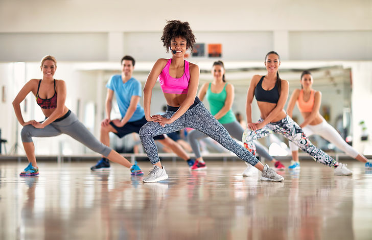 _Pretty fitness trainer show aerobic exercises to fitness group.jpg