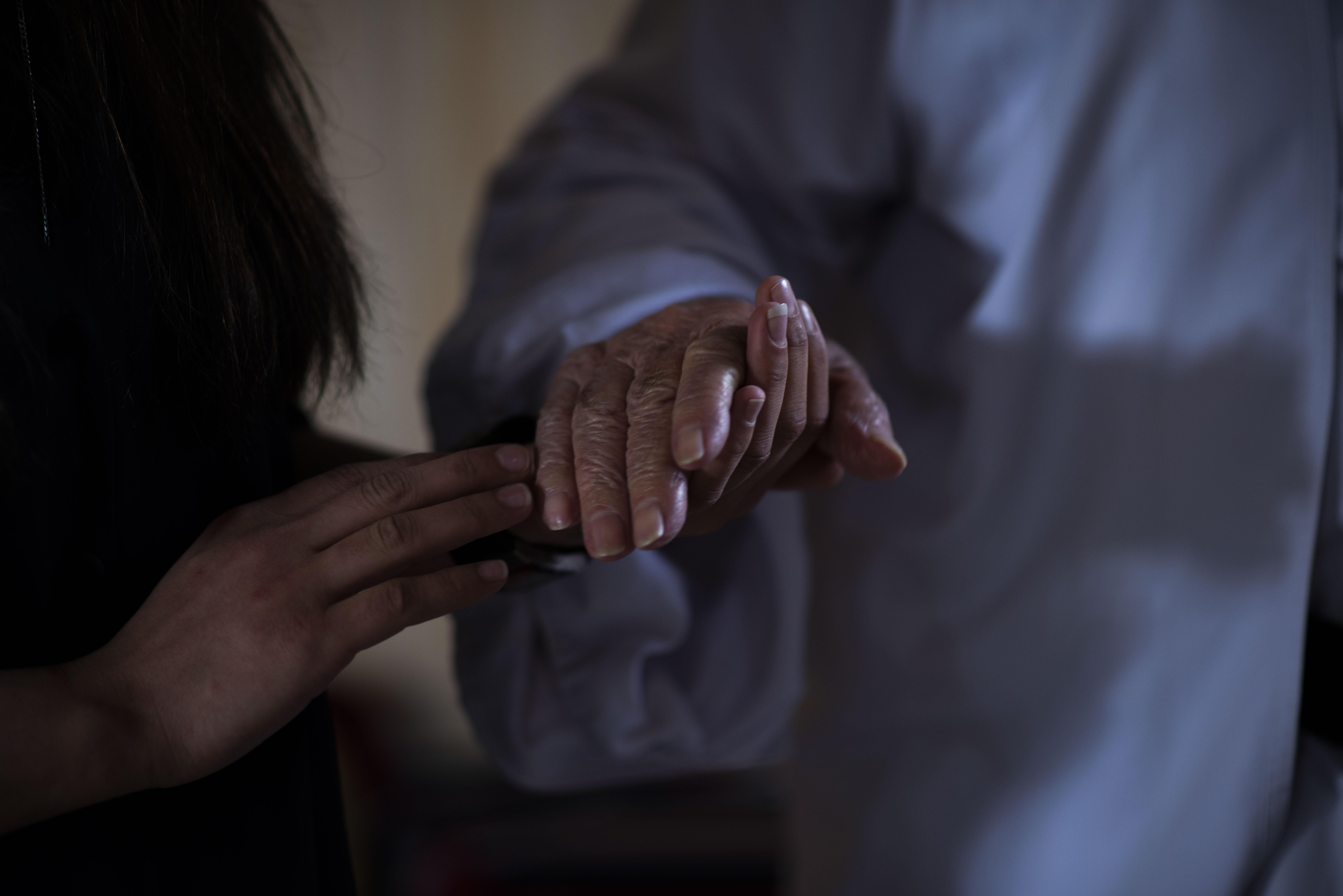 A Yazidi woman and ISIS survivor strokes the hand of Baba Sheik, the spiritual leader of the Yazidi
