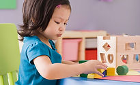 Girl playing with shape sorter in preschool