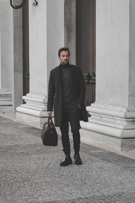 Chelsea Boots, Anzughose, Rollkragen Pullover und Mantel und als Accessoire einen Weekender