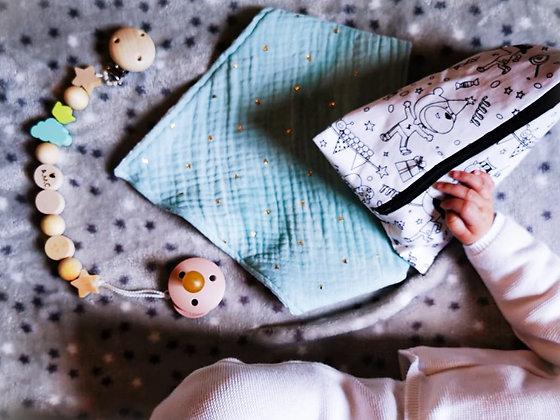 bébé qui tiens une pochette à colorier, un bavoir et un attache tétine DIY de la box cadeau de naissance DIY Bo'kit