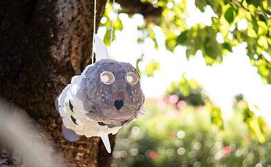 Pinata en forme de poisson accrochée à un arbre. Fabriqué avec le kit créatif DIY pinata.