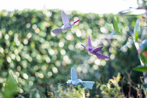 On peut voir le mobile décoratif Bo'kit composé de trois oiseaux en papier maché suspendu dans un jardin