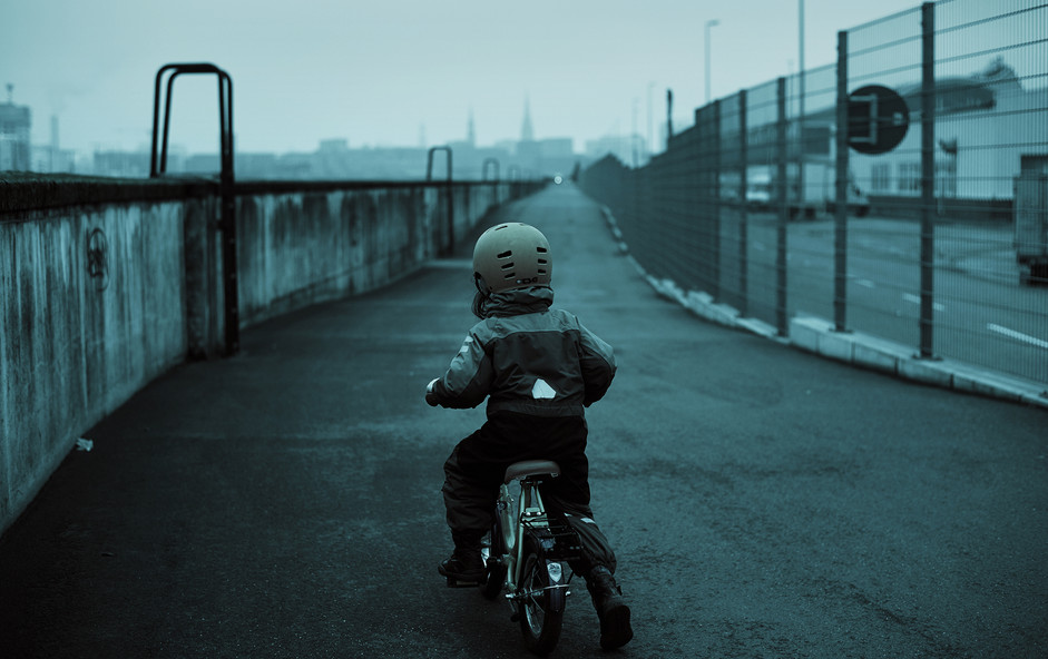 Kid with bike in empty cold city