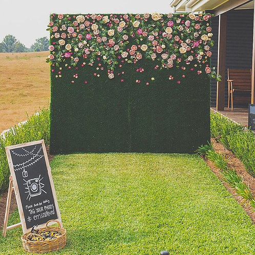 Free standing wall with life like turf and pastel blooms