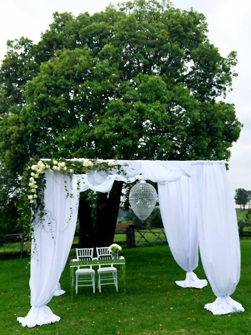 White 4 post arbour draped in white chiffon with blooms