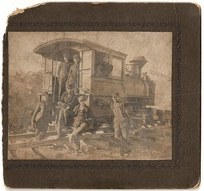 Workers next to locomotive at quarry near Mt. Union, PA