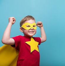 Little child superhero with yellow cloak