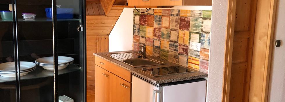 Küchenzeile mit Kühlschrank, Herd, Einbauschränken und Spüle
