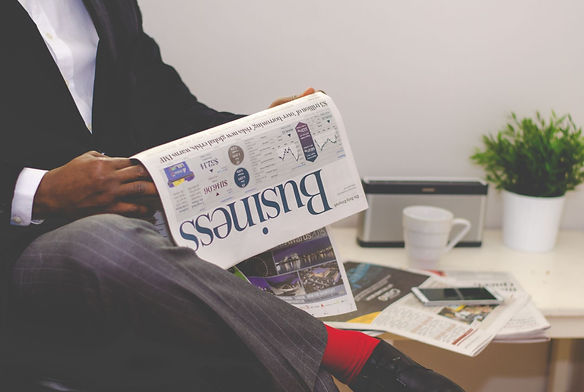 man with crossed leg, red socks, reading the business news