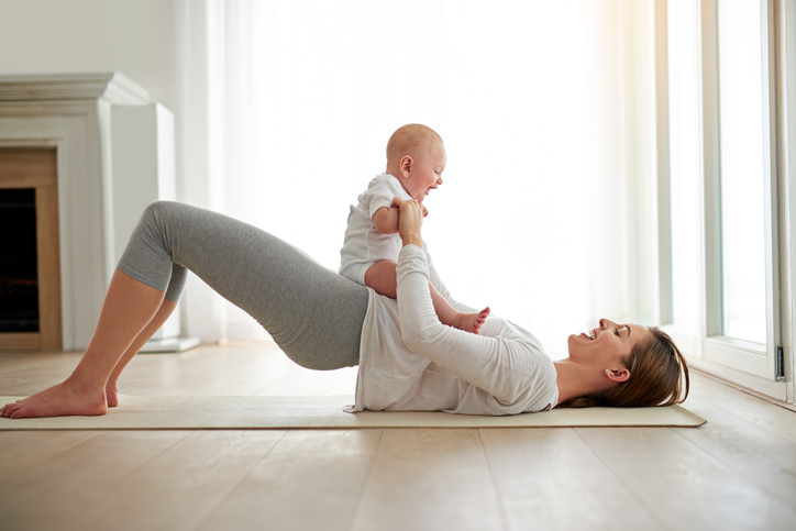 mom doing glute bridge with baby