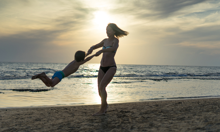 mom spinning child on the beach