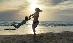 mom spinning child on the beach