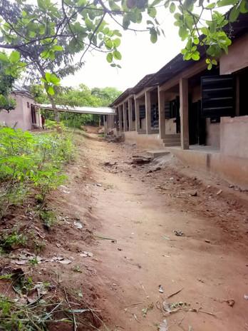 Hier sieht man die direkte Verbindung von den Klassenräumen zu den Toiletten.  Der betonierte Gang wurde überdacht, damit auch bei schlechtem Wetter die Kinder sowie auch die Klassenräume geschützt werden.