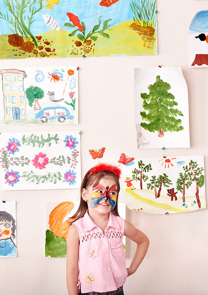 Girl with paint on face and artwork behind her. Happy after Play Therapy   Play Therapy in St. Louis, MO 63011