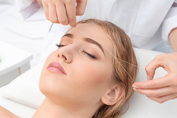 Young woman having eyebrow correction pr