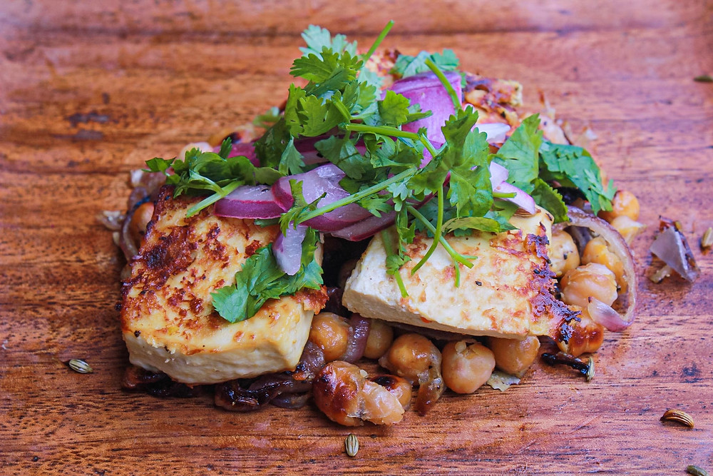 Baked tofu, garbanzos, onion, and cilantro dish on wooden plate