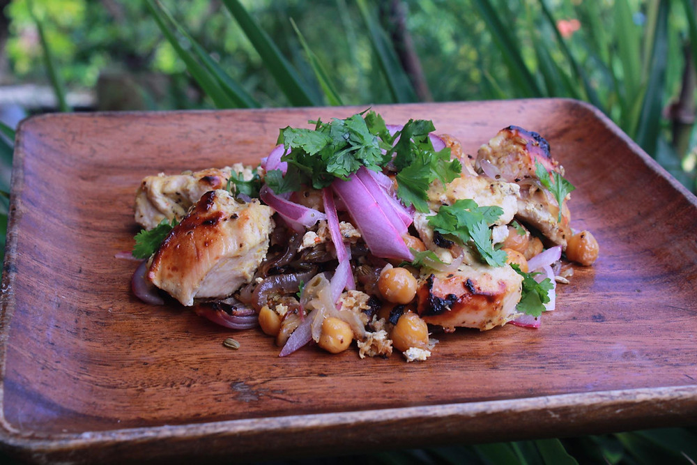 Wooden plate with baked chicken, chickpeas, onions and cilantro