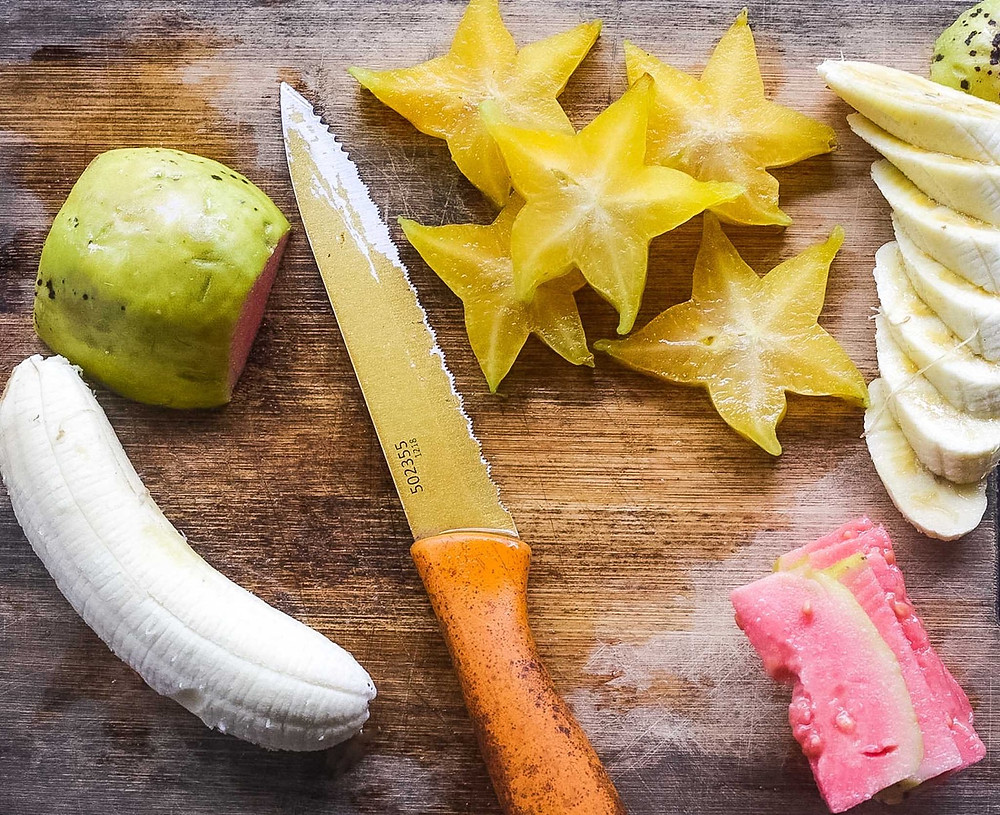 Wood cutting board with tropical fruits - banana, guava, star fruit - and a knife