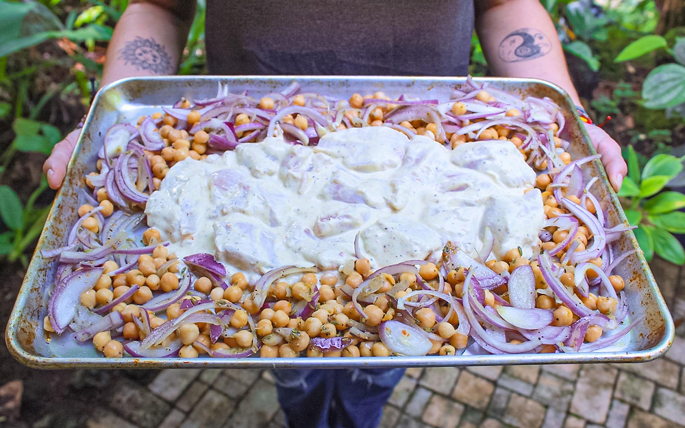 Hands hold a sheet pan covered in chickpeas, onions, and chicken marinated in yogurt