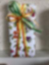 長方形の箱をかわいいフルーツの包装紙でラッピング。リボンはオレンジと黄色のストライプをV字かけにしてあります。