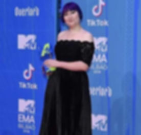 Ellen Jones in a black dress holding her MTV EMA award on the red carpet.