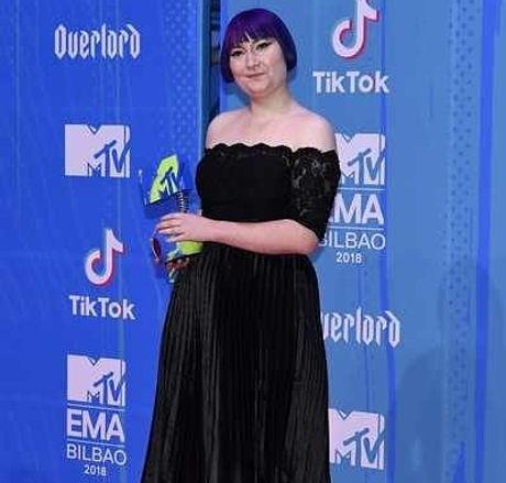 Ellen Jones in a black dress holding her MTV EMA award on the red carpet.