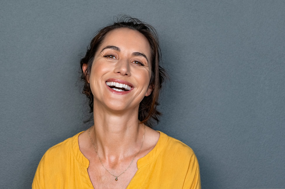 Portrait of mature woman laughing agains