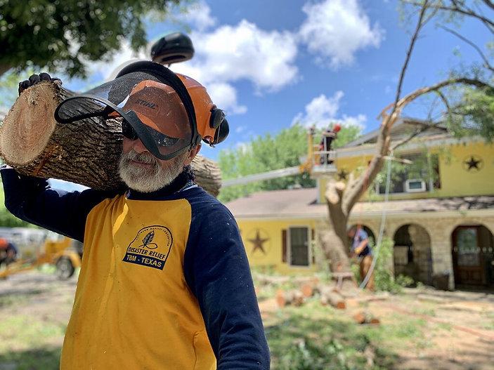 tbm-disaster-relief-volunteer-carries-heavy-log-after-san-antonio-tornado.jpg