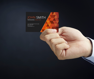 A man displaying the business card of his company.