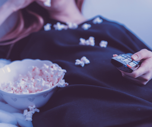 A woman lying down and watching her favorite movie with a tub of popcorn and a remote in her hand.