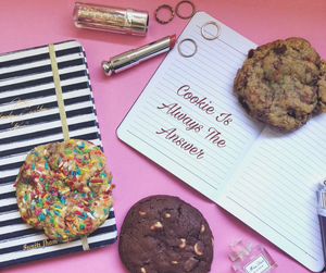 Quarter Pound Cookies made by Pretty Baked Dubai on a desk over some notebooks.