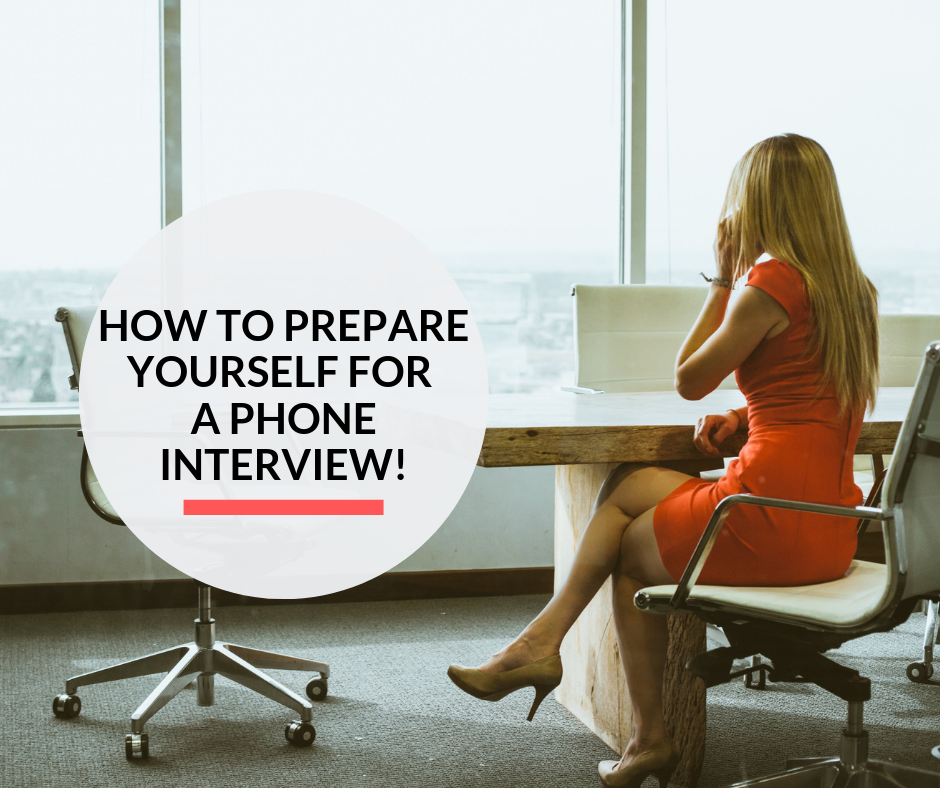 An interviewer interviewing a candidate over a phone interview in an office.