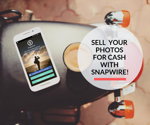 A smartphone besides a cu of tea on a motorbike, displaying the Snapwire app.