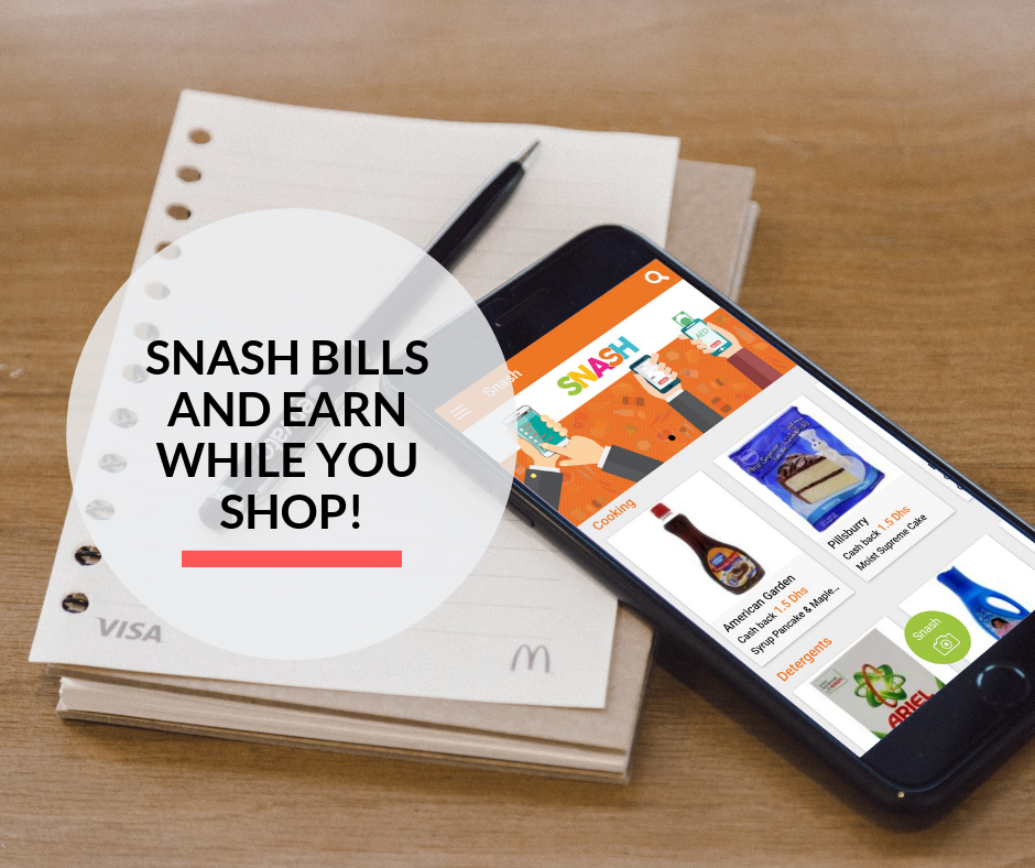 A smartphone on top of a notebook and pen, displaying the snash app to earn cashback on groceries.
