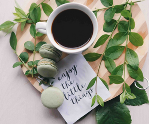 A cup of tea on a board with a note that says enjoy the little things.