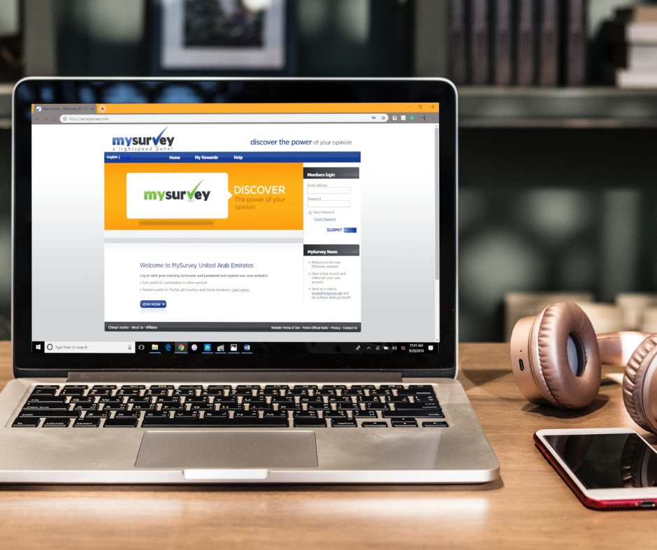 A laptop displaying an opened browser of the My Survey UAE website with headphones beside it.