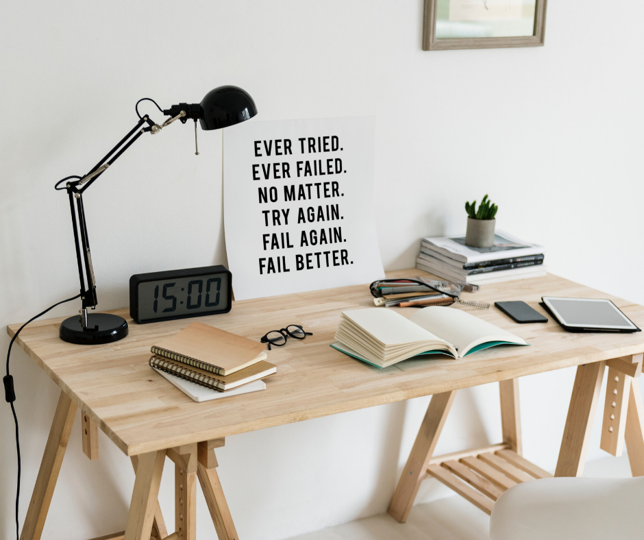 A motivational poster in front of a work desk at home.