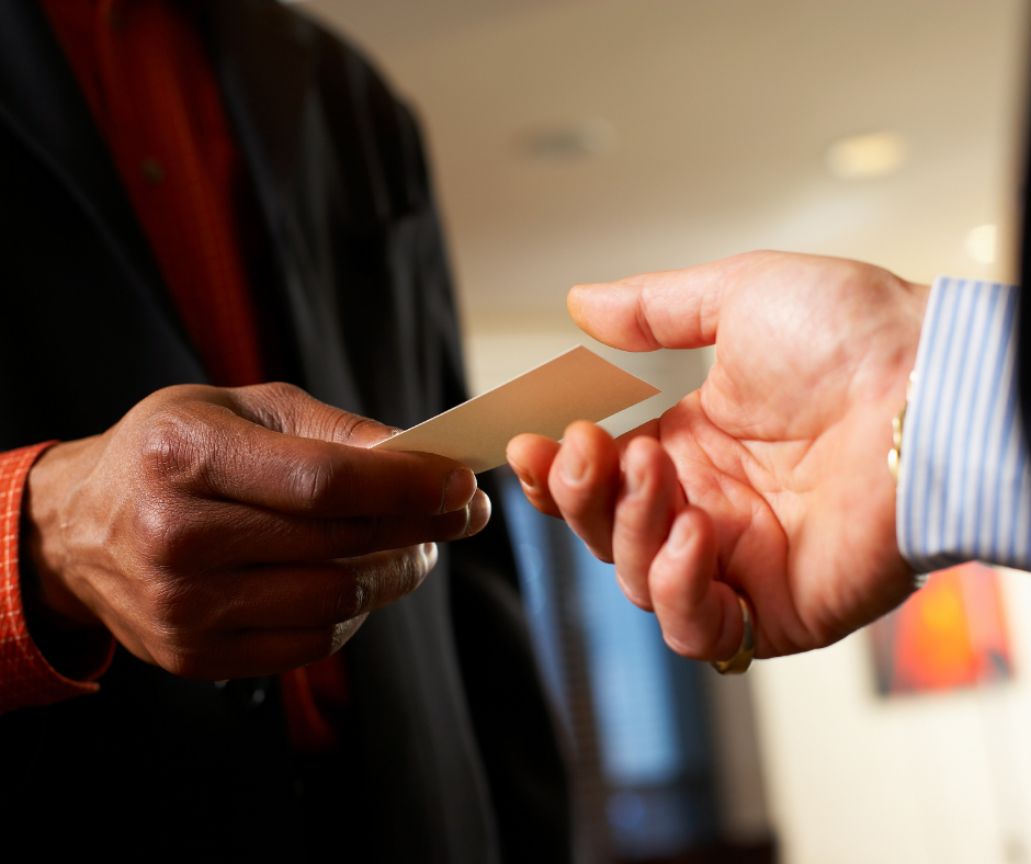 A man handing out his business card to another at a networking event.