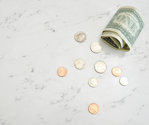 Coins and notes scattered as expenses for personal finances.
